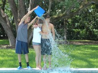 Junior Brian Gerstien and senior Corina Scheuren do the ice bucket challenge. Frehsman Trahern Gribble  pours the ice over their heads with a wry smile.